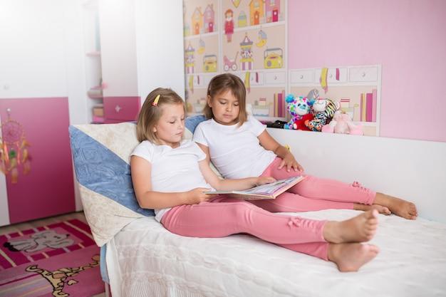 Feche o retrato de meninas adoráveis caucasianos lendo livro juntos no quarto acolhedor Foto Premium