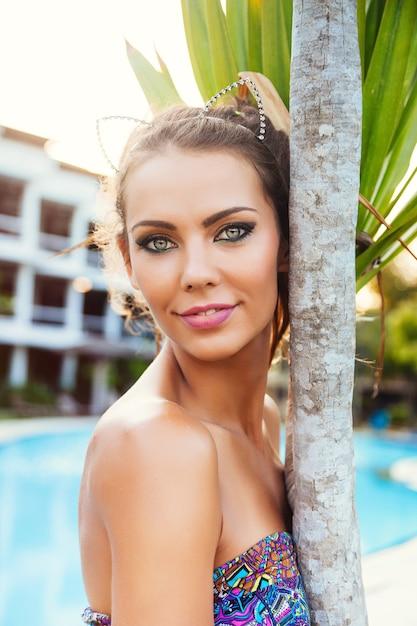 Feche o retrato de moda ao ar livre de uma linda mulher bronzeada com aparência elegante de olhos esfumados brilhantes, vestido colorido brilhante e coroa de diamantes, posando perto de votação no verão. Foto gratuita