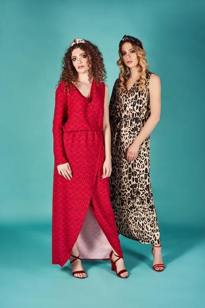 Feche o retrato de moda interior de mulheres lindas em elegantes vestidos de vermelho e leopardo. loiras e morenas meninas isoladas na parede turquesa. tiro completo de modelos encaracolados contentes Foto Premium