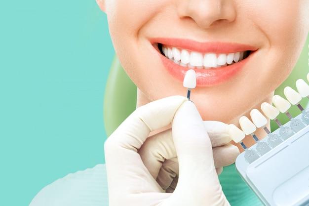 Feche o retrato de mulheres jovens na cadeira do dentista, verifique e selecione a cor dos dentes. clareamento dos dentes Foto Premium