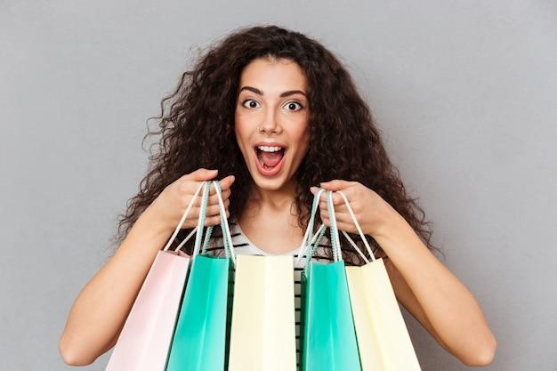 Feche o retrato de shopaholic feminino animado fazendo compras, sendo feliz e encantado para comprar produtos favoritos, segurando compras nas mãos Foto gratuita