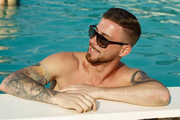 Feche o retrato de um homem barbudo bonito em óculos de sol sorrindo olhando para longe Foto Premium