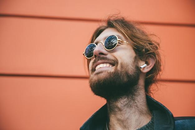 Feche o retrato de um homem barbudo feliz em fones de ouvido Foto gratuita