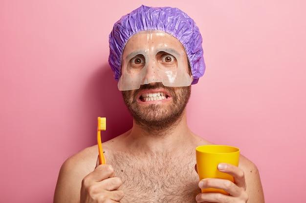 Feche o retrato de um homem bonito segurando uma escova de dentes e um copo amarelo, está com os ombros nus e uma máscara no rosto Foto gratuita
