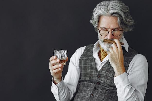 Feche o retrato de um homem sorridente à moda antiga. avô com um charuto e uísque. Foto gratuita