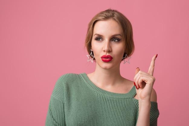 Feche o retrato de uma jovem bonita isolada em um fundo rosa, pensando, tendo uma ideia, segurando o dedo, estilo elegante, lábios vermelhos, tendência da moda de primavera, expressão de carinha engraçada Foto gratuita