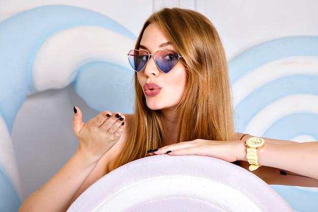 Feche o retrato de uma jovem feliz posando no estúdio perto de doces enormes, cabelos longos e sorriso de beleza, usando óculos escuros e relógios, estilo pop. Foto gratuita