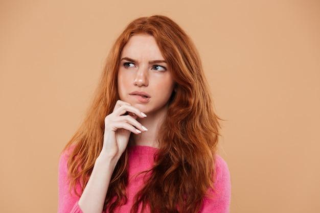 Feche o retrato de uma jovem ruiva pensativa Foto gratuita