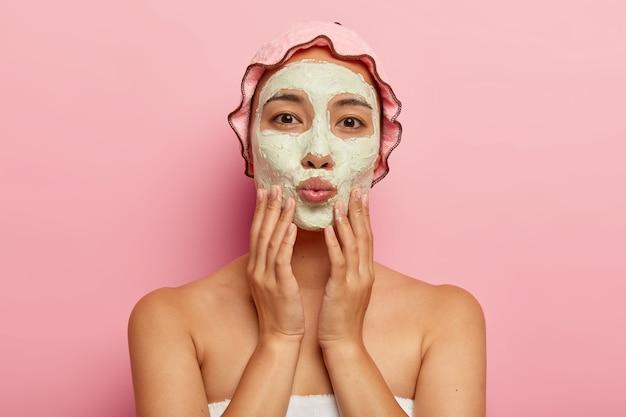 Feche o retrato de uma linda mulher asiática com máscara facial cosmética, toca o rosto suavemente, mantém os lábios dobrados, olha diretamente, gosta de limpeza e tratamentos de beleza. rotina de cuidados com a pele Foto gratuita
