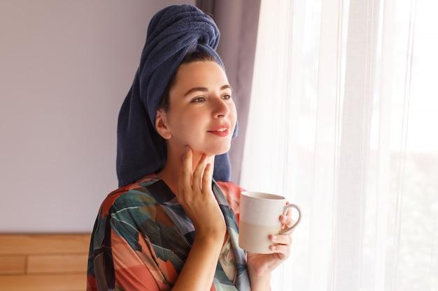 Feche o retrato de uma linda mulher envolvida em toalha e roupão, acordando de manhã sentado na cama e tomando café Foto gratuita