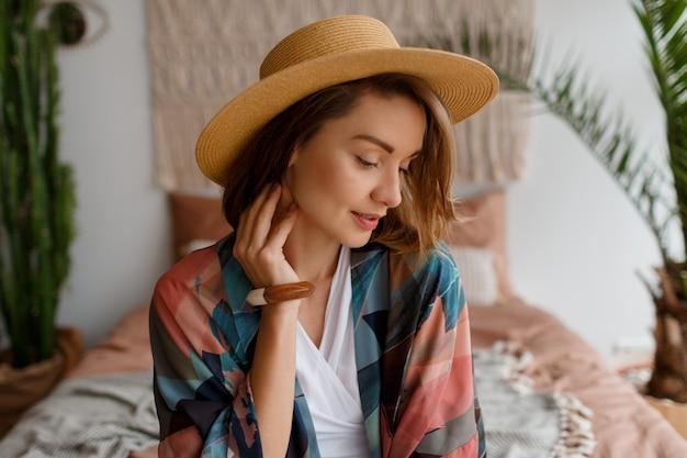 Feche o retrato de uma linda mulher romântica no chapéu de palha relaxando no interior boêmio Foto gratuita