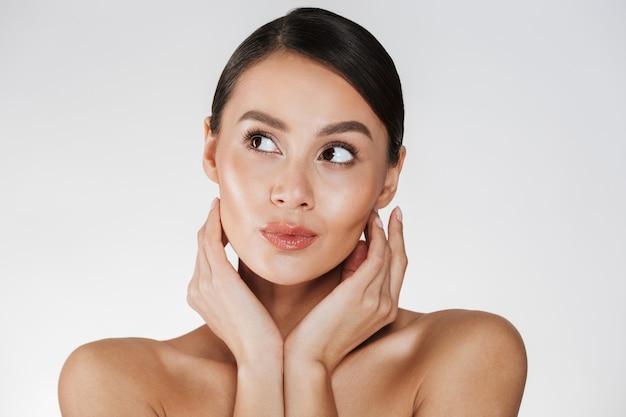 Feche o retrato de uma mulher bonita com maquiagem natural, olhando de lado e segurando as mãos perto de seu rosto saudável, isolado sobre o branco Foto gratuita