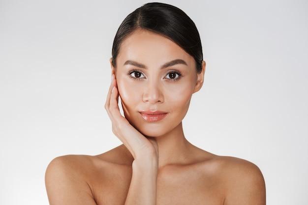 Feche o retrato de uma mulher bonita com maquiagem natural, posando para a câmera com toque no rosto, isolado sobre o branco Foto gratuita