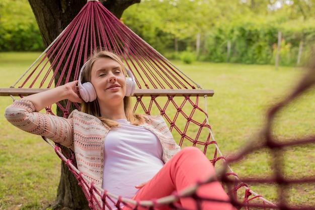 Feche o retrato de uma mulher deitada na rede, ouvindo música com o telefone celular. a menina alegre goza na rede hammock ao ar livre. mulher relaxante, fora, ouvindo música com fones de ouvido Foto gratuita
