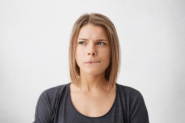 Feche o retrato de uma mulher jovem e bonita com penteado bob mordendo os lábios e olhando de soslaio com expressão pensativa e duvidosa enquanto ela tem que tomar uma decisão importante, posando para uma parede em branco Foto gratuita