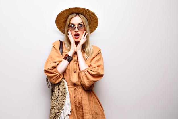 Feche o retrato de uma mulher loira bonita usando chapéu de palha e roupa boho Foto gratuita