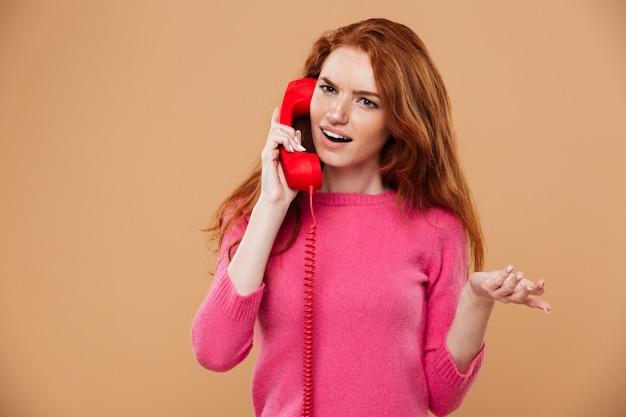 Feche o retrato de uma ruiva bonita confusa falando pelo telefone vermelho clássico Foto gratuita