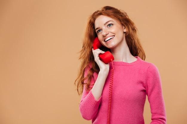 Feche o retrato de uma ruiva bonita sorridente, falando por telefone vermelho clássico Foto gratuita