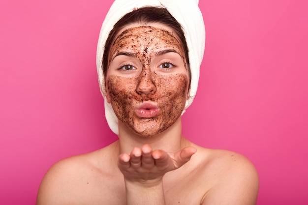 Feche o retrato do belo europeu feminino mandando beijo, colocando a máscara de chocolate, estar nu, penteando o cabelo com uma toalha branca, parece calmo e relaxado. conceito de beleza e cuidados. Foto gratuita