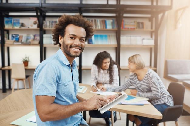 Feche o retrato do estudante universitário bonito sentado na reunião com os amigos após o estudo Foto gratuita