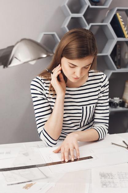 Feche o retrato do freelancer bonito jovem arquiteto feminino com cabelos longos escuros na camisa listrada, sentado à mesa branca no espaço de coworking, olhando através de plantas que ela já fez, pensando Foto gratuita