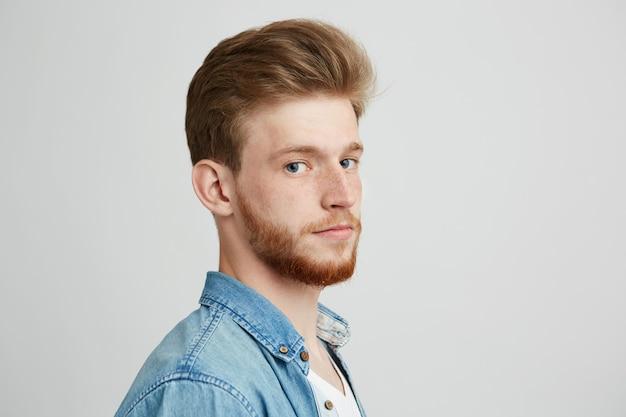Feche o retrato do homem jovem bonito hipster com barba, vestindo camisa jeans. Foto gratuita