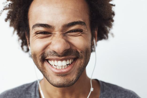 Feche o retrato do jovem africano feliz sorrindo ouvindo otimista streaming música rindo. conceito de juventude. Foto gratuita