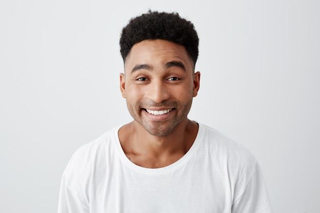 Feche o retrato isolado de alegre jovem feliz com penteado afro em casual camiseta branca sorrindo brilhantemente, olhando na câmera com expressão animada e alegre. Foto gratuita