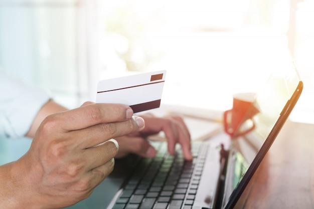 Feche o tiro ao lado do jovem empresário trabalhando em seu laptop e usando o cartão de crédito sentado na mesa de madeira em um café com tom de cor de filtro vintage Foto Premium