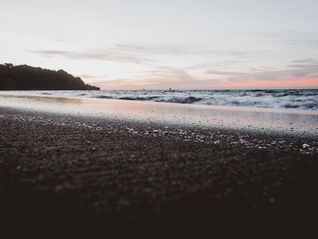 Feche o tiro de uma praia sob um céu nublado Foto gratuita