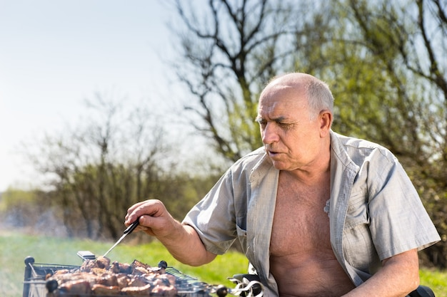 Feche o velho sério com camisa aberta grelhados na área do acampamento enquanto está sentado em sua cadeira de rodas em uma manhã muito ensolarada. Foto Premium
