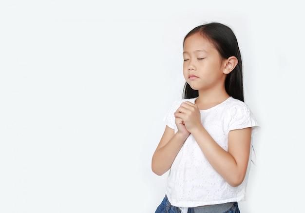 Feche os olhos que rezam a menina asiática pequena bonita da criança isolada com espaço da cópia. conceito de espiritualidade e religião. Foto Premium