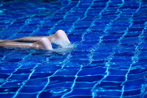 Feche os pés de criança na piscina, flutuando na água azul refrescante e azulejo. Foto Premium