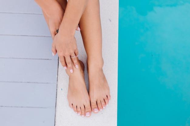Feche os pés e as mãos da mulher. mulher sentada à beira de uma piscina azul de férias Foto gratuita