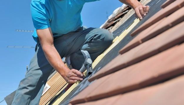 Feche um trabalhador segurando um martelo e reformando o telhado de uma casa Foto Premium