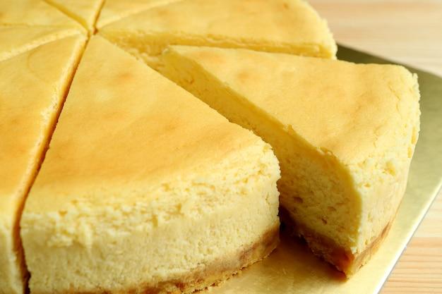 Fechou um pedaço de cheesecake cozido amarelo cremoso cortado do bolo todo Foto Premium