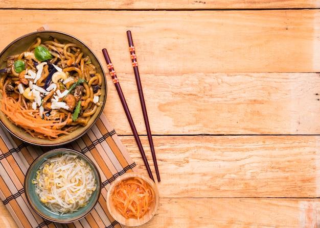 Feijão de brotos; cenoura ralada e macarrão com pauzinhos sobre a mesa de madeira Foto gratuita