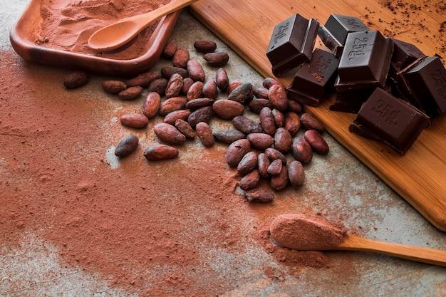 Feijão de cacau cru e pó com cubos de chocolate Foto gratuita
