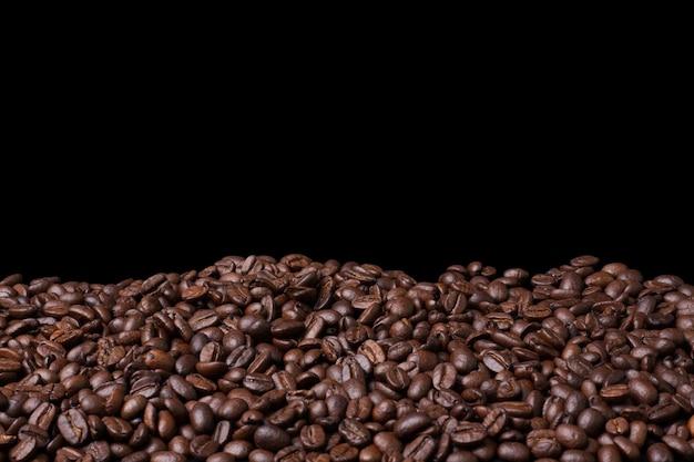 Feijão de café fresco closeup em fundo preto Foto Premium
