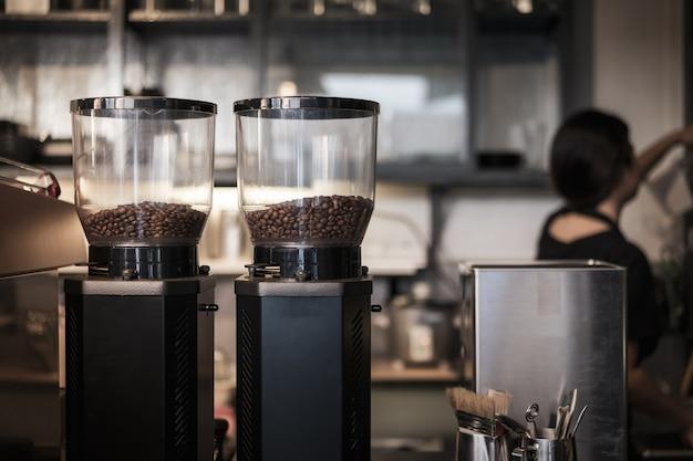 Feijão de café na máquina de café na cafetaria. Foto Premium