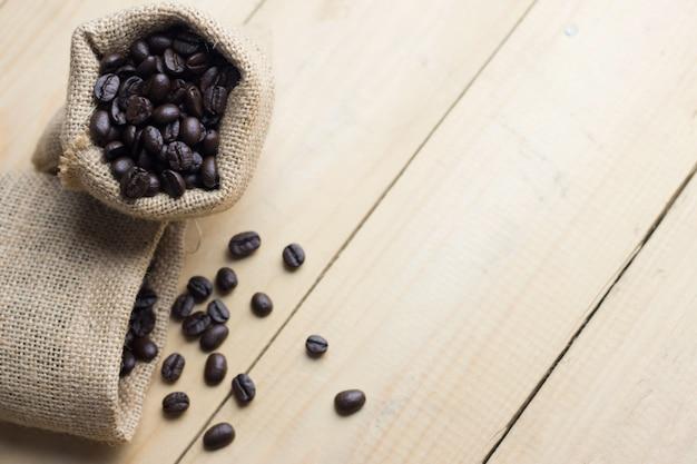 Feijão de café no saco na tabela de madeira. visão de alto ângulo Foto Premium