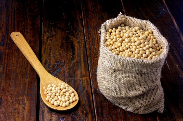 Feijão de soja cru e fresco no saco de tecido rústico na mesa de madeira Foto Premium
