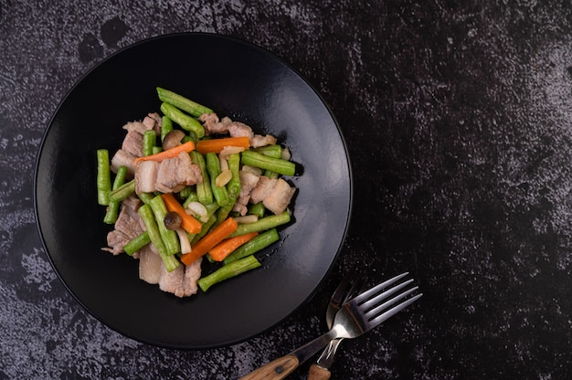 Feijão frito e cenoura, adicione a barriga de porco, coloque em um prato preto. Foto gratuita