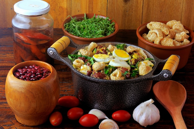 Feijão tropeiro prato típico da culinária brasileira, feita com feijão, bacon, linguiça, couve, ovos, mesa de madeira rústica. Foto Premium