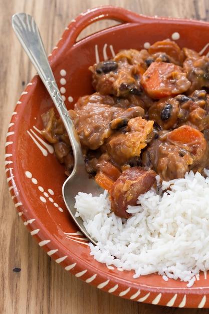 Feijoada de prato típico português com arroz em uma tigela de cerâmica na mesa de madeira marrom Foto Premium