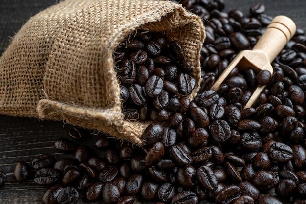 Feijões de café do close up no saco feito da serapilheira na pá de superfície e de madeira de madeira que encontra-se em um saco. Foto Premium