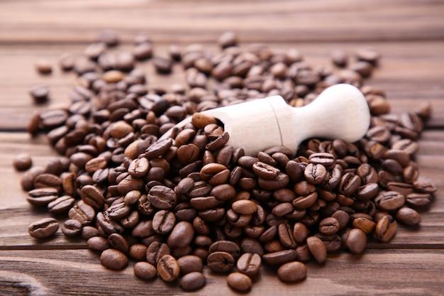 Feijões de café na colher de madeira no fundo marrom. Foto Premium