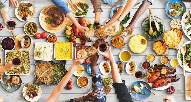 Felicidade de amigos, aproveitando o conceito de comer de jantar Foto Premium