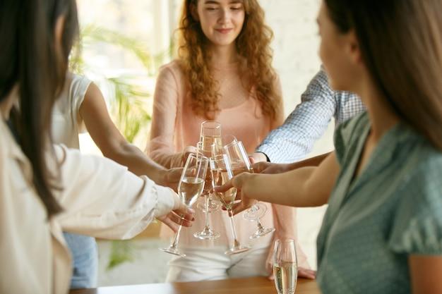 Felicidade. pessoas tilintando taças com vinho ou champanhe. Foto gratuita