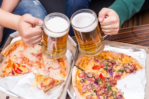Felicidades. vista superior de homens com copos de cerveja e pizza Foto gratuita